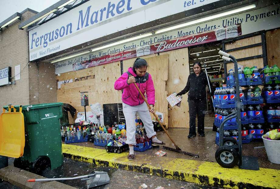 Anjana Patel cleans up the damage from Monday's riots at her store, Ferguson Market and Liquor, Wednesday, Nov. 26, 2014, in Ferguson, Mo.  A grand jury's decision not to indict a police officer in the shooting death of an unarmed 18-year-old has stoked passions nationwide, triggering debates over the relations between black communities and law enforcement.  (AP Photo/David Goldman) Photo: David Goldman / Associated Press / AP