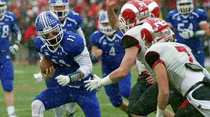 Darien's Timothy Graham carries the ball during the FCIAC championship game between New Canaan High School and Darien High School in Stamford, Conn., on Thanksgiving Day, Thursday, November 27, 2014.