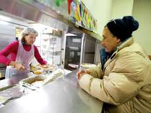 Benjamin Rodriguez gets a Thanksgiving meal from Anna Fratczak at Pacific House homeless shelter in Stamford, Conn., on Thanksgiving Day, Thursday, November 27, 2014.