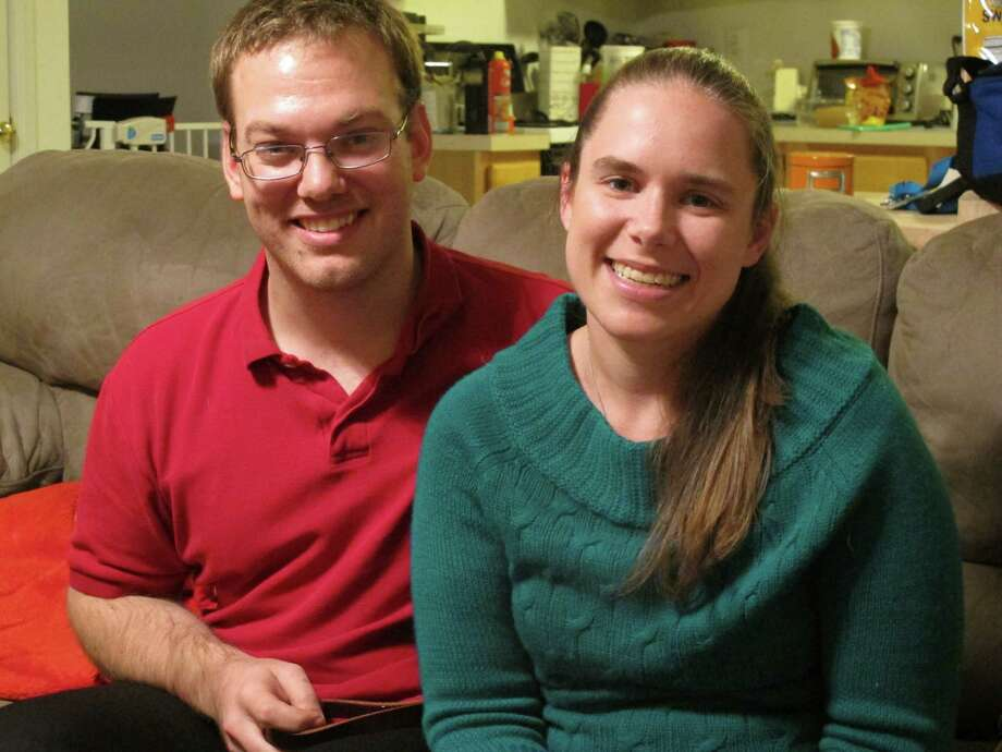 In this Tuesday, Nov. 25, 2014, photo, Alyssa Riggan, who was the first in the United States to successfully receive a liver from a living donor 25 years ago, poses with her husband, Benjamin, in their home in Severn, Md. As Riggan marks the 25th anniversary of her successful surgery on Thursday, she says its success has enabled her to live a normal life almost completely untouched by what was an often-fatal disorder. Riggan was 21 months old when her mother, Teri Smith, donated more than a third of her liver to save her daughter from a disorder called biliary atresia. (AP Photo/ Brian Witte) Photo: Brian Witte / Associated Press / AP