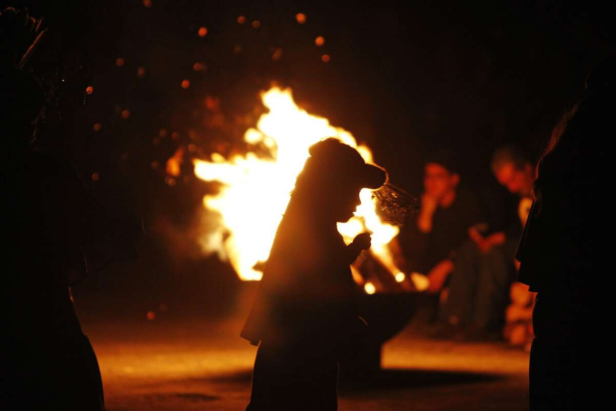 A young participant dances around a bonfire at the beginning of theIndigenous Peoples' Day Sunrise Gatheringon Alcatraz Island on November 27, 2014 in San Francisco, Calif.