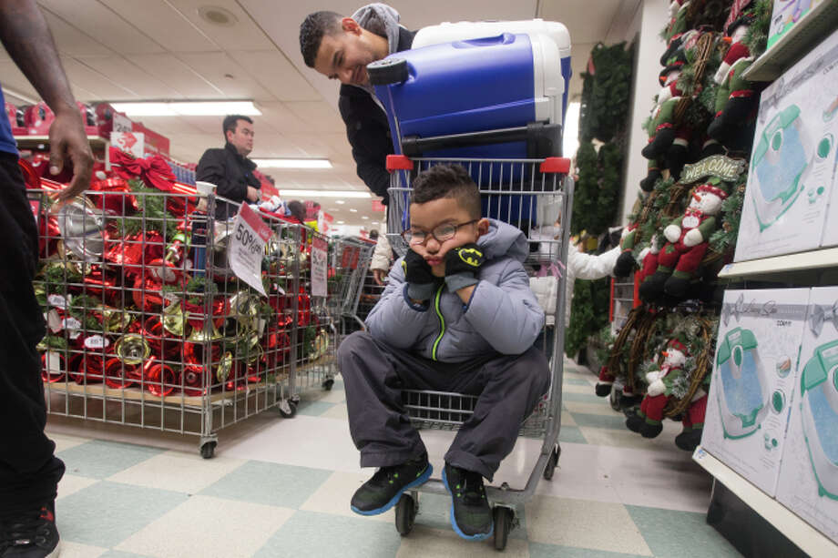 Dylan Morales pouts while his dad, Rigoberto, fills a shopping cart at Kmart in New York. Photo: John Minchillo / Associated Press / FR170537 AP