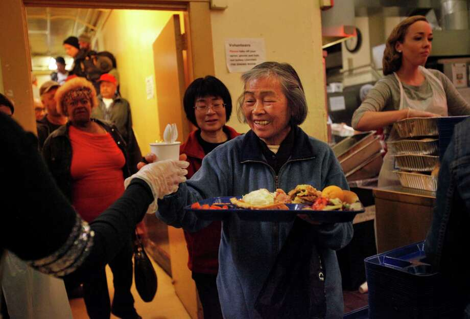 Yiau smiles as she receives plasticware with her meal at Glide Memorial Church during their annual Thanksgiving dinner Nov. 27, 2014 in San Francisco, Calif. The church served nearly 5,000 Thanksgiving meals to people in the community throughout the day. Photo: Leah Millis / The Chronicle / ONLINE_YES