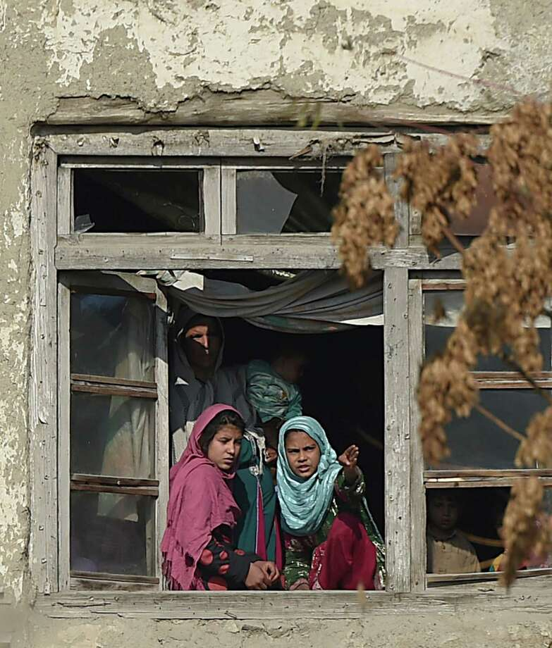 Afghan residents look on from the window of their house at the scene of a suicide attack along the Kabul-Jalalabad road in Kabul on November 27, 2014. At least two Afghan bystanders were killed when a suicide bomber on a motorbike attacked a British embassy vehicle in Kabul on November 27, injuring some passengers, officials said. AFP PHOTO/SHAH MaraiSHAH MARAI/AFP/Getty Images Photo: SHAH MARAI / AFP/Getty Images / AFP