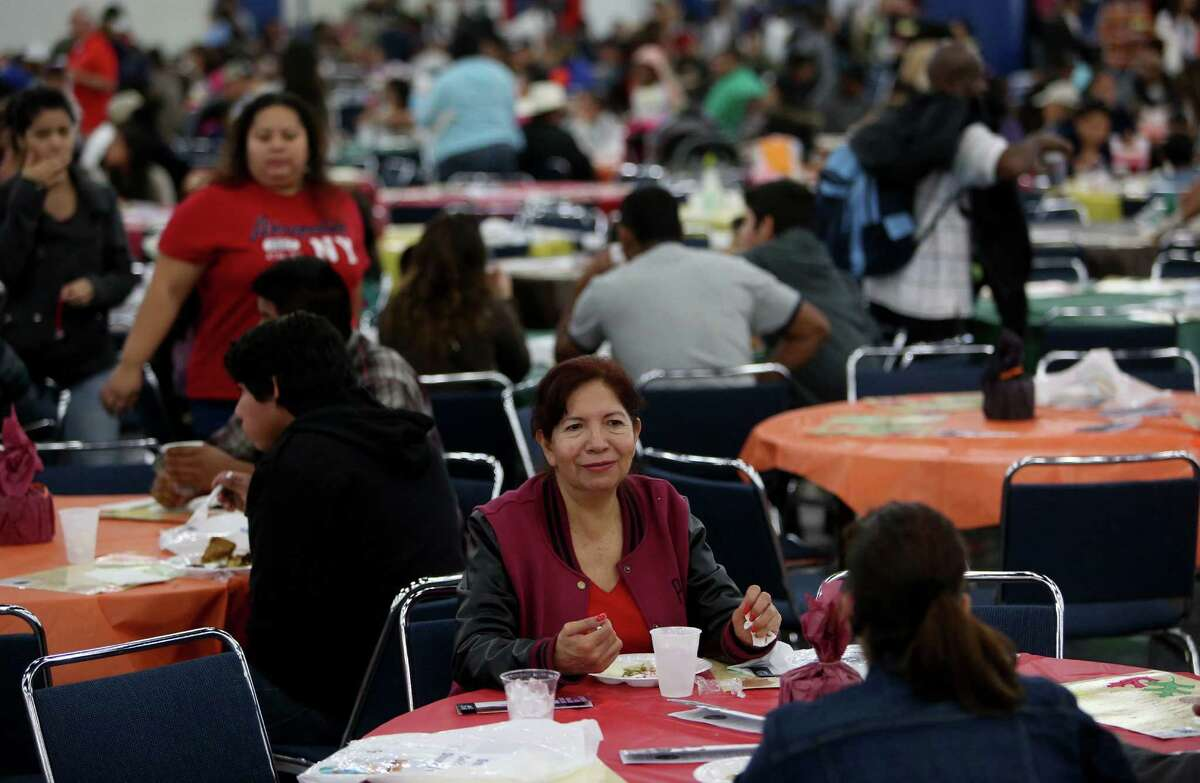 Maria Elena Alvarez enjoys a meal at the 36th Annual Thanksgiving Big Feast presented by the City Wide Club at the George R. Brown Convention Center Thursday, Nov. 27, 2014, in Houston, Texas. Organizers expect to serve between 25,000 and 30,000 people, distribute more than 500,000 pieces of clothing, blankets, jackets and other household items and offer free medical screenings.