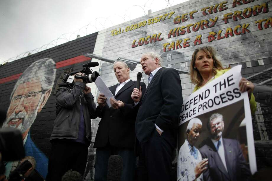 FILE - A Saturday, May 3, 2014 photo from files showing Sinn Fein's Martin McGuinness, centre, with party members Bobby Storey, left, and Martina Anderson speaking during a protest rally on the Falls Road, West Belfast, Northern Ireland. A prominent Irish Republican Army veteran has been arrested on suspicion of involvement in the IRA's 1972 abduction, killing and secret burial of a widowed mother of 10, one of the outlawed group's most notorious slayings. The Irish nationalist Sinn Fein party says its Northern Ireland chairman, Bobby Storey, was arrested Wednesday, Nov. 26, 2014. Police say he's being interrogated about the killing of 38-year-old Jean McConville, whose remains were found bear an Irish beach in 2003. (AP Photo/Peter Morrison, File) Photo: Peter Morrison / Associated Press / AP