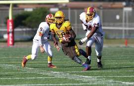 Mission Bear's Anthony Porter, # 10 a junior, runs from two Lincoln defenders during the Annual Turkey Day game for the SF Championship with the Mission Bears against the Lincoln Mustangs at Lowell High School in San Francisco, Calif., on Thursday November 27, 2014.