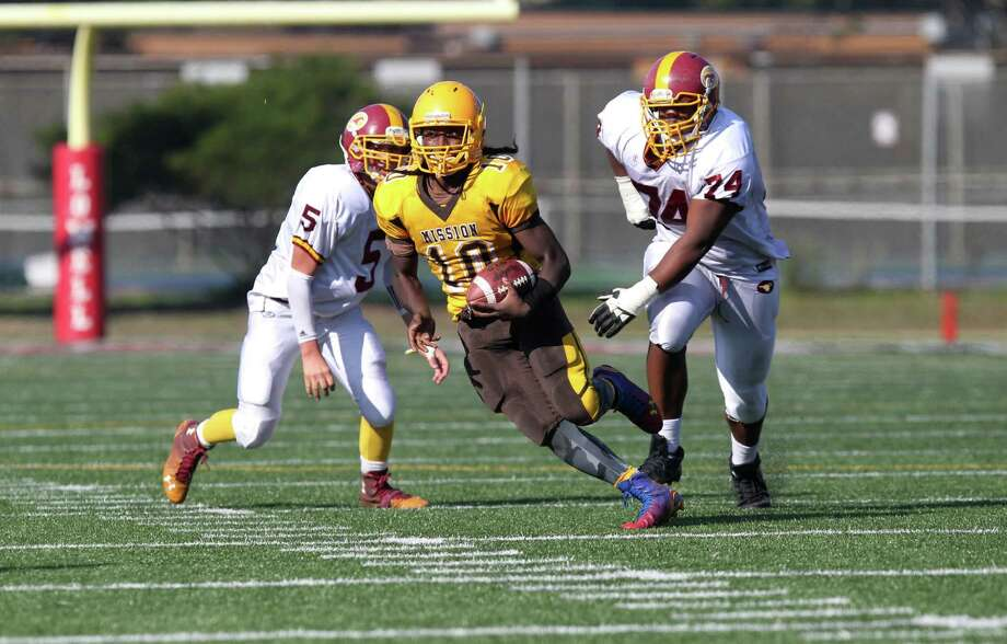Mission Bear's Anthony Porter, # 10 a junior, runs from two Lincoln defenders during the Annual Turkey Day game for the SF Championship with the Mission Bears against the Lincoln Mustangs at Lowell High School in San Francisco, Calif., on Thursday November 27, 2014. Photo: Daniel E. Porter / The Chronicle / ONLINE_YES