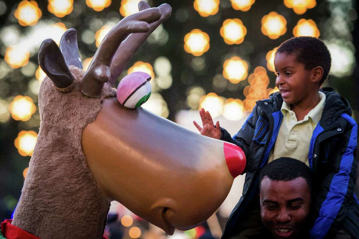 Jordan Jenkins, 4, gets face to face with a reindeer from atop Charles Nesmith's shoulders during the annual Uptown Houston Holiday Lighting on Thursday, Nov. 27, 2014, in Houston.