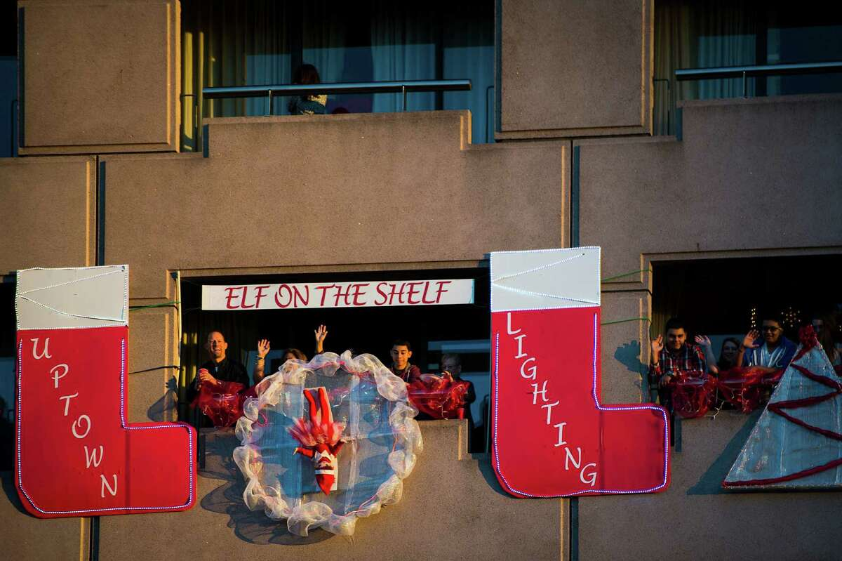 Revelers wave from decorated balconies of the Hilton Post Oak hotel during the annual Uptown Houston Holiday Lighting on Thursday, Nov. 27, 2014, in Houston.