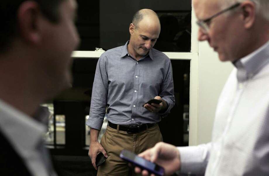 L-R, Sean Clegg, Dan Newman, and Ace Smith check their smarphones in their offices at SCN Strategies in San Francisco, Calif., on Sunday, November 23, 2014. The 2014 elections marked a dismal result for democrats across the nation, but local political strategists Ace Smith, Dan Newman, and Sean Clegg, notched a perfect 10 for 10 with wins in big races for clients like Jerry Brown, Kamala Harris, Libby Schaff, and Gavin Newsom. Photo: Carlos Avila Gonzalez / The Chronicle / ONLINE_YES