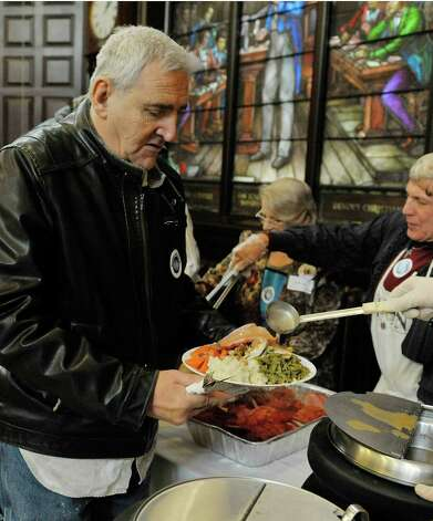 Robert Burg of Albany gets his food at the annual Equinox Thanksgiving Day Community Dinner at the First Presbyterian Church on Thursday, Nov. 27, 2014, in Albany, N.Y.  (Paul Buckowski / Times Union) Photo: Paul Buckowski / 00029628A