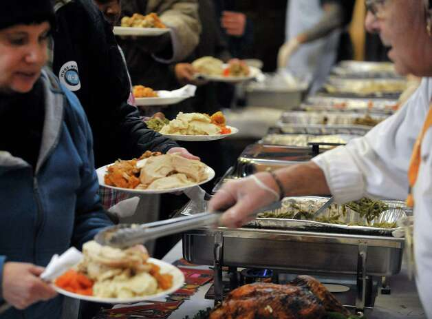 Volunteers dish out food to guests at the annual Equinox Thanksgiving Day Community Dinner at the First Presbyterian Church on Thursday, Nov. 27, 2014, in Albany, N.Y.  (Paul Buckowski / Times Union) Photo: Paul Buckowski / 00029628A