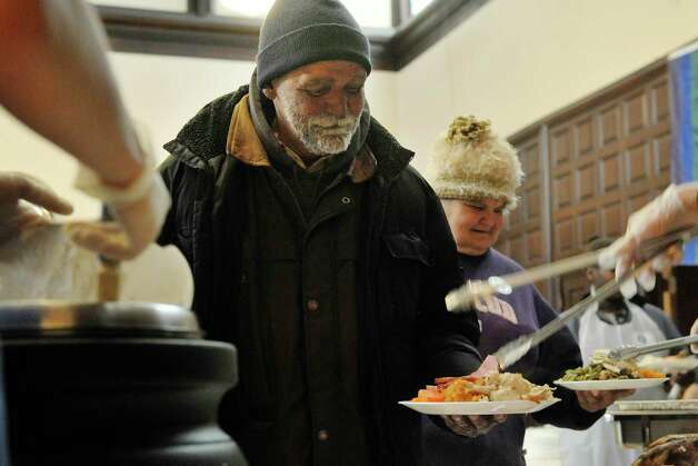Joe Walden of Albany gets ham placed onto his plate as he got his food at the annual Equinox Thanksgiving Day Community Dinner at the First Presbyterian Church on Thursday, Nov. 27, 2014, in Albany, N.Y.  (Paul Buckowski / Times Union) Photo: Paul Buckowski / 00029628A