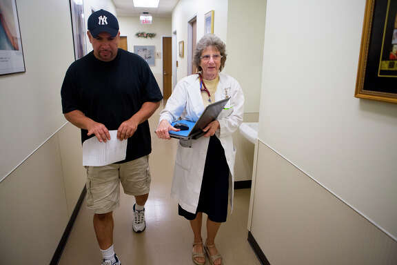 Sister Rosanne Popp, medical director at a Christus Foundation clinic in southwest Houston, walks patient Willie Dana out after a visit. The clinic charges a flat $35 for appointments and $10 for labs.