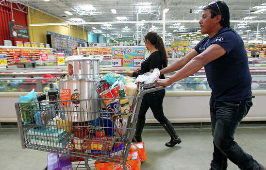 Claudia and Juan Lopez stride into the meat section after getting a steamer and other supplies as shoppers gather last minute items for the Thanksgiving holiday at the HEB at 6818 South Zarzamora on November 27, 2014. Photo: TOM REEL