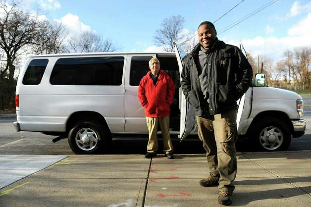 Staff van driver Rolensky Alphonse, right, and volunteer Ismael Munoz stand by the new outreach van on Tuesday, Nov. 18, 2014, at the Homeless Action Committee in Albany, N.Y. The 2014 Ford van was purchased with money raised from an online fundraising campaign Alphonse started when the old van broke down. (Cindy Schultz / Times Union) Photo: Cindy Schultz / 00029497A