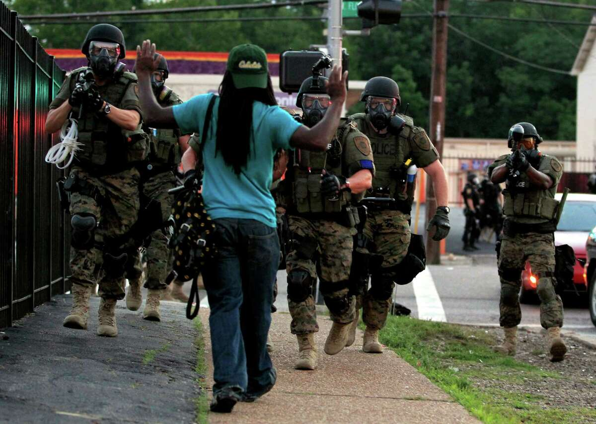 FILE- In this Aug. 11, 2014 photo, police wearing riot gear point their weapons before arresting a man in Ferguson, Mo. ?'Hands Up, Don?'t Shoot?' has become a rallying cry despite questions whether Michael Brown?'s hands were raised in surrender before being fatally shot by a Ferguson police officer. (AP Photo/Jeff Roberson, File) ORG XMIT: NY690