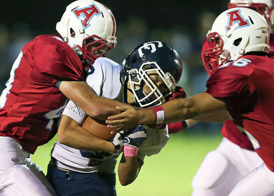 Button quarterback Jimin Suh gets caught between Apache tacklers Steven Wynn (left) and Kyle Cantu as Antonian hosted Central Catholic at Ferrara Stadium on October 17, 2014. Photo: TOM REEL / TOM REEL / San Antonio Express-News / San Antonio Express-News