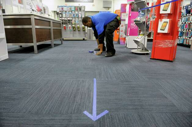 Ishmael Allah, a mobile consultant at Best Buy creates arrows for customer to line up on and follow on the floor in the mobile phone department before the doors open during their Thanksgiving Day sale on Thursday, Nov. 27, 2014, in Albany, N.Y. (Paul Buckowski / Times Union) Photo: Paul Buckowski / 00029656A