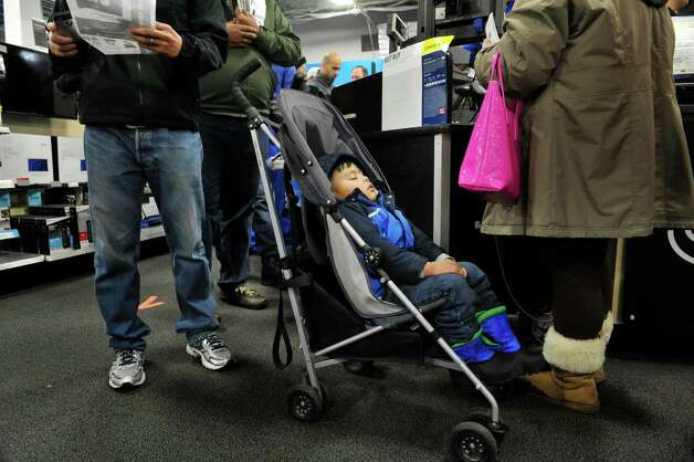 A.J. Malaza, 3, of Albany sleeps in his stroller as his parents buy a television at Best Buy during their Thanksgiving Day sale on Thursday, Nov. 27, 2014, in Albany, N.Y. (Paul Buckowski / Times Union) Photo: Paul Buckowski / 00029656A
