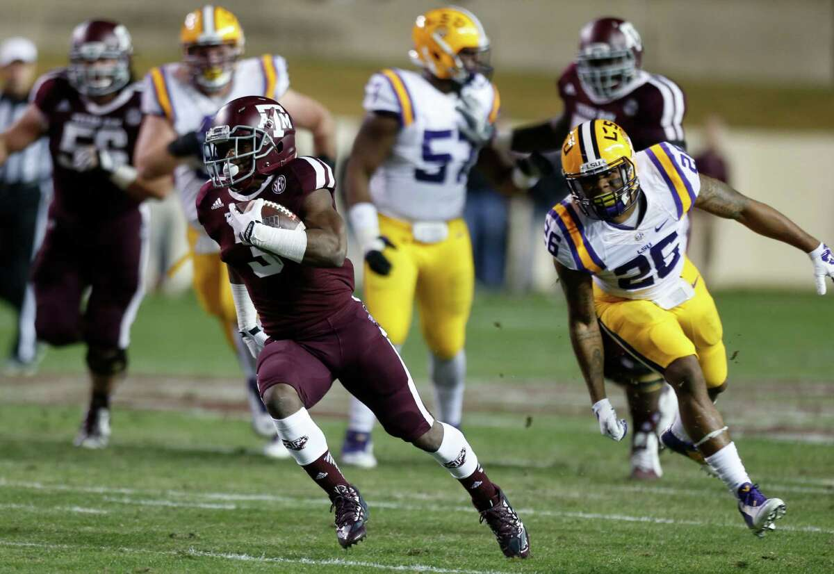 Texas A&M running back Trey Williams, left, breaks away from LSU safety Ronald Martin for a 41-yard touchdown run, one of the few highlights for the Aggies, who lost to the Tigers for the fourth straight time.
