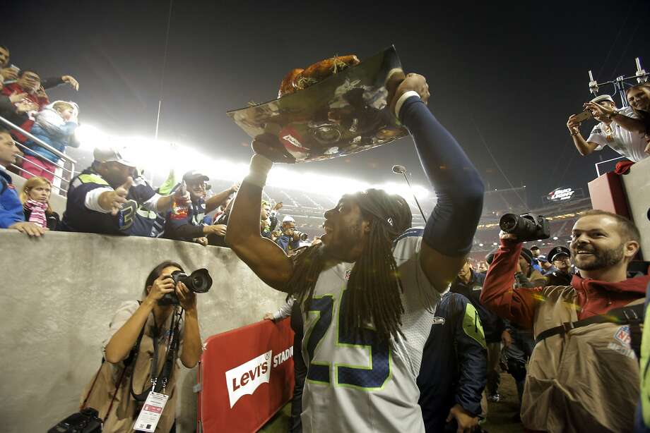 Richard Sherman (25) carries a Thanksgiving turkey off the field at Levi's Stadium after the 49ers played lost to the Seattle Seahawks 19-3, in Santa Clara, Calif., on Thursday, November 27, 2014. Photo: Carlos Avila Gonzalez, The Chronicle
