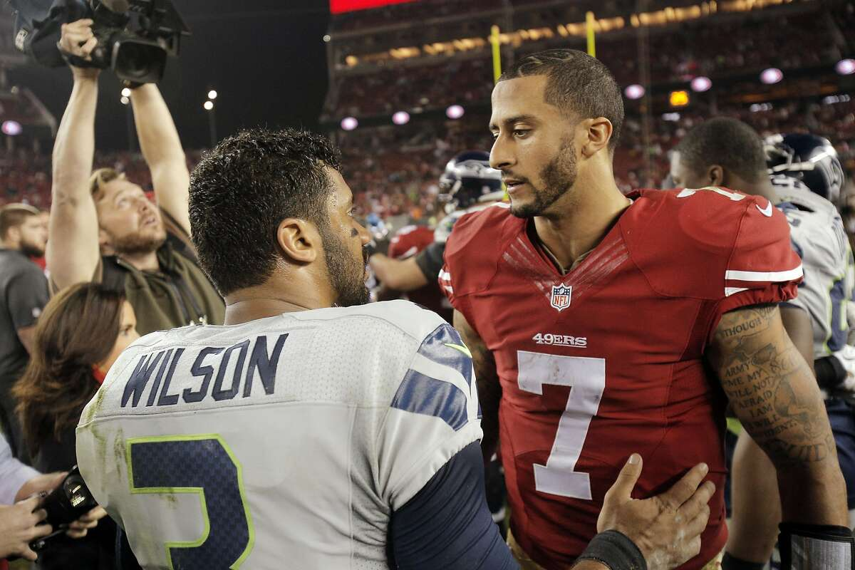 Russell Wilson (3) and Colin Kaepernick (7) talk at midfield after the Seahawks defeated the 49ers 19-3 at Levi's Stadium in Santa Clara, Calif., on Thursday, November 27, 2014.
