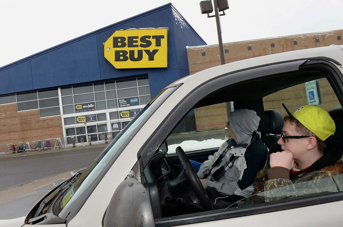 Jake Baker, right, and Chris Flores, watch their chairs marking their spots in line as they keep warm in their truck waiting for Best Buy in Wilton, NY, to open on Thanksgiving night, Thursday, Nov. 27, 2014. The pair has been waiting since 8 a.m. for the 5 p.m. opening, but have kept an eye on the store since 11 p.m. last night from a nearby hotel room they rented. (AP Photo/The Daily Gazette, Patrick Dodson) TROY, SCHENECTADY; SARATOGA SPRINGS; ALBANY AND AMSTERDAM OUT