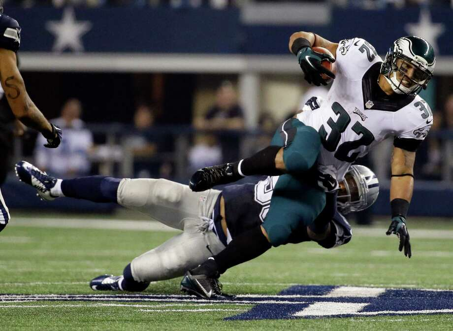 Anthony Hitchens takes down Chris Polk during the second half. Photo: Tony Gutierrez, STF / Associated Press / A