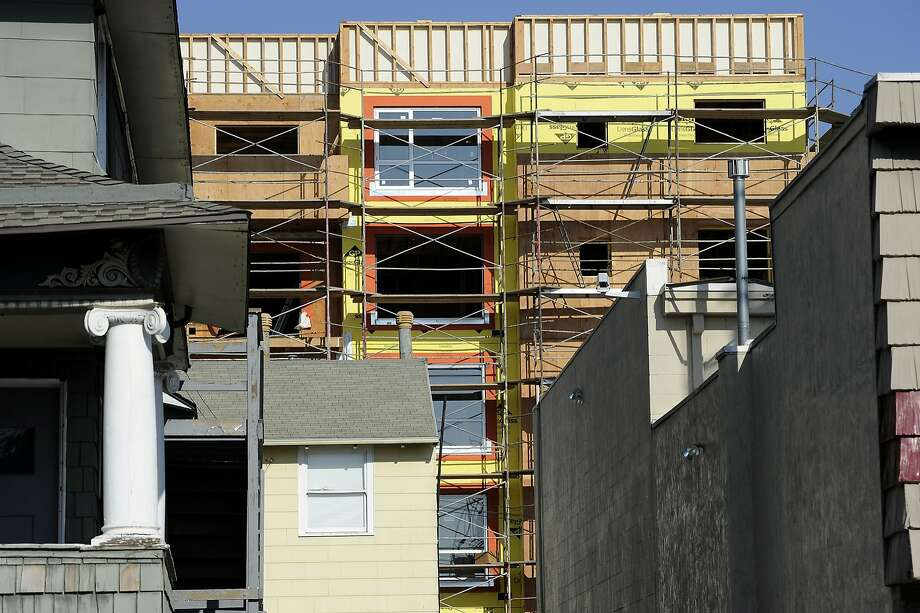 The new MacArthur Transit Village, which will offer affordable and market rate housing, rises up behind existing homes next to the MacArthur BART Station in Oakland, CA, on Wednesday, November 26, 2014. Photo: Michael Short, Special To The Chronicle
