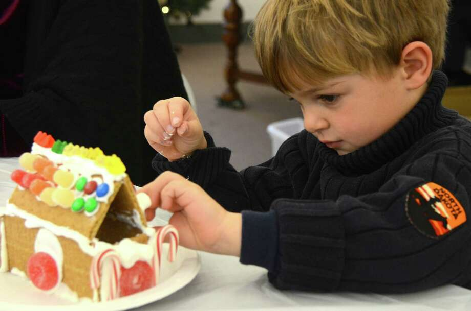 Lars Gertzen adds some color and candy to his gingerbread house at the New Canaan Historical Society on Saturday, Dec. 7, 2013. Photo: Jeanna Petersen Shepard / New Canaan News