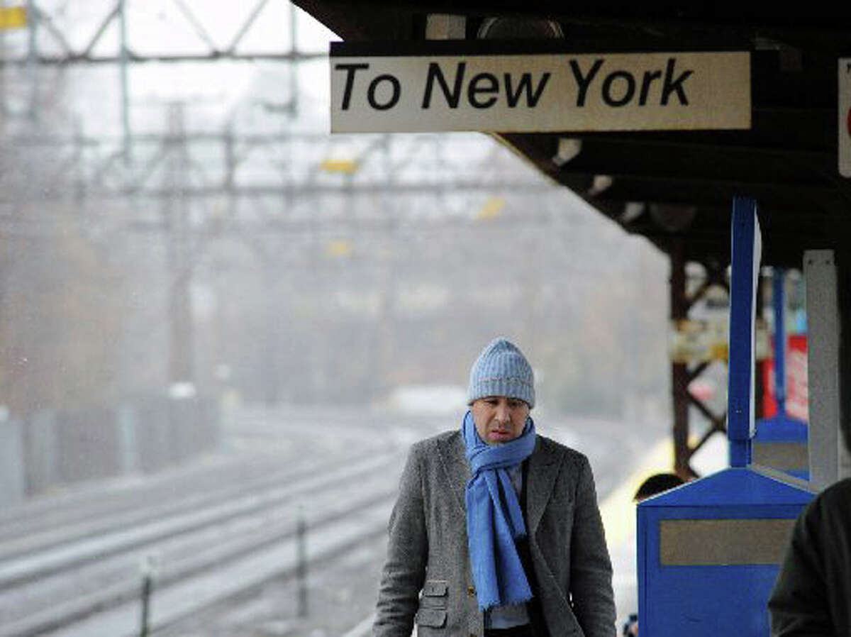 A man wearing a winter hat and scarf walks along the platform of the Greenwich Train Station during the first winter storm of the season in Greenwich, Conn., Wednesday, Nov. 26, 2014.