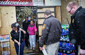 Anjana Patel and her son Kush, rear, watch as law enforcement officials arrive to investigate the looting at their store as they clean up the damage from Monday's riots following a grand jury's decision not to indict a police officer in the shooting death of an unarmed 18-year-old, Wednesday, Nov. 26, 2014, in Ferguson, Mo. The racially charged case has stoked passions nationwide, triggering debates over the relations between black communities and law enforcement. (AP Photo/David Goldman)