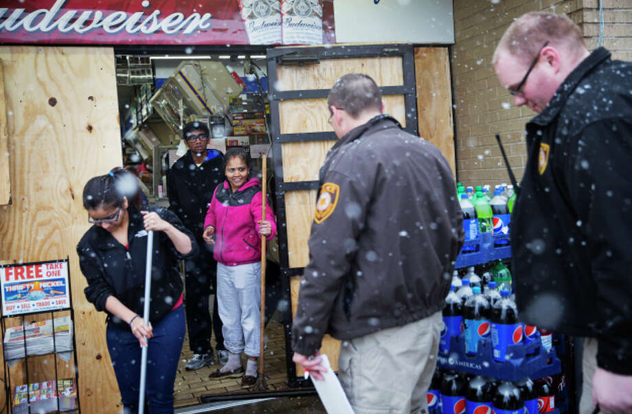 Anjana Patel and her son Kush, rear, watch as law enforcement officials arrive to investigate the looting at their store as they clean up the damage from Monday's riots following a grand jury's decision not to indict a police officer in the shooting death of an unarmed 18-year-old, Wednesday, Nov. 26, 2014, in Ferguson, Mo. The racially charged case has stoked passions nationwide, triggering debates over the relations between black communities and law enforcement. (AP Photo/David Goldman) Photo: David Goldman / Associated Press / AP