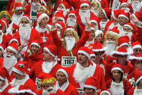 NEWTOWN, UNITED KINGDOM - DECEMBER 04: Runners dressed as Father Christmas are seen at the start of the Santa fun run on December 04, 2005 in Newtown, Powys, Wales. The run, which started in 2001 with just a handful of entrants, raises money for the local Newton and District Dial a Ride. (Photo by Matt Cardy/Getty Images)