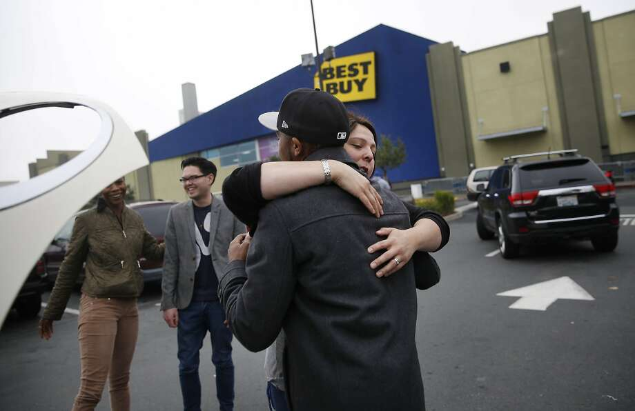 Jennifer Gunn (second from right) and Terrence Strickland (right) hug goodbye as Amanda Gardner (left) thanks James Dohnert (second from left) after all helped Gardner along with Ryan Kurth (not shown), all of San Francisco, helped Gardner push or  provided a jump for the car after noticing that Gardner's car had died in the Best Buy parking lot on Black Friday on Friday, November 28, 2014 in San Francisco, Calif. Gunn, Strickland, Dohnert and Gardner had all finished shopping but Kurth said he was going back in for the second time. Photo: Lea Suzuki, The Chronicle