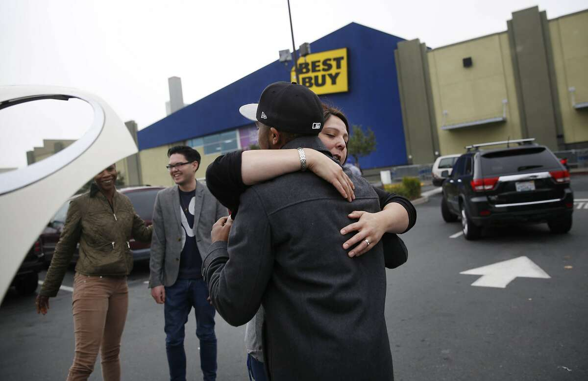 Jennifer Gunn (second from right) and Terrence Strickland (right) hug goodbye as Amanda Gardner (left) thanks James Dohnert (second from left) after all helped Gardner along with Ryan Kurth (not shown), all of San Francisco, helped Gardner push or provided a jump for the car after noticing that Gardner's car had died in the Best Buy parking lot on Black Friday on Friday, November 28, 2014 in San Francisco, Calif. Gunn, Strickland, Dohnert and Gardner had all finished shopping but Kurth said he was going back in for the second time.