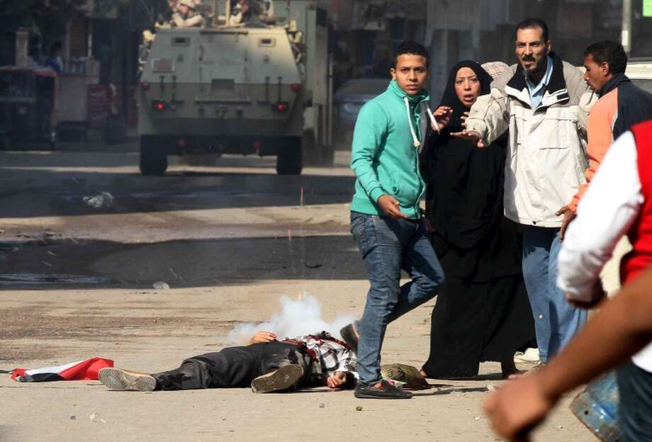Egyptians react next to a man who was shot in Cairo during clashes between protesters and police. Photo: KHALED KAMEL / AFP/Getty Images / AFP
