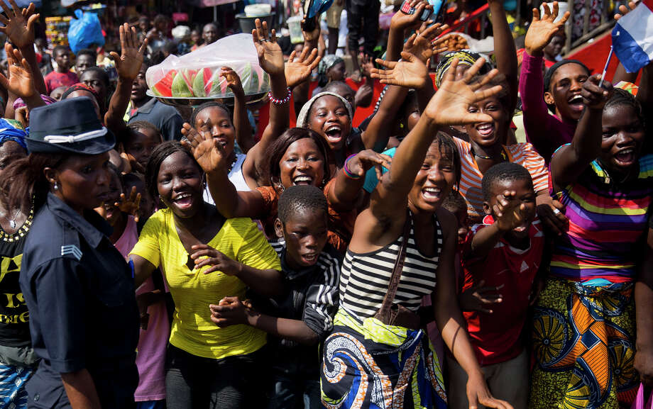 People cheer the motorcade carrying French President Francois Hollande and his Guinean counterpart, Alpha Conde, in Conakry, Guinea. Photo: Jerome Delay / Associated Press / AP