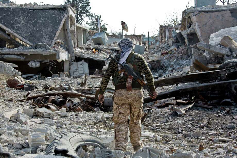 A Kurdish fighter shows the extent of the damage from a truck bomb in Kobani, Syria. Kurdish fighters backed by small numbers of Iraqi peshmerga forces and Syrian rebels, are battling Islamic State militants who swept into their town in mid-September as part of a summer blitz that saw the group seize large chunks of territory in Syria and neighboring Iraq. Photo: Jake Simkin / Associated Press / AP