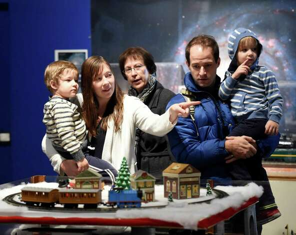 The Glennon family of Cape Elizabeth, Maine, enjoys the train display, part of the Trains and Toys display at the Museum of Innovation and Science, Friday morning, Nov. 28, 2014 in Schenectady, N.Y. The Glennons from left;  Jack, 3; Mom Lauren; grandmother Eileen Eldred of Niskayuna;  dad Aron Glennon and Henry, 3.   The Trains and Toys show runs until Jan. 19, 2015.       (Skip Dickstein/Times Union) Photo: SKIP DICKSTEIN / 00029626A