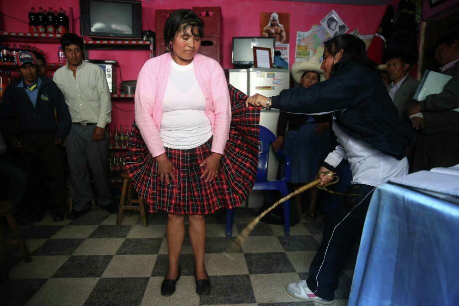 """In this May 8, 2014 photo, Maria Vera stands still as she is lashed five times by a member of a citizen enforcers band known as """"rondas urbanas,"""" or urban patrols, as punishment for having an affair with a married man, in Cajamarca, Peru. The rondas take on cases that authorities consider minor, settling property and debt disputes, family quarrels and marital infidelities. Adulterous spouses typically get several lashings and an order to be faithful. (AP Photo/Martin Mejia) Photo: Martin Mejia / Associated Press / AP"""