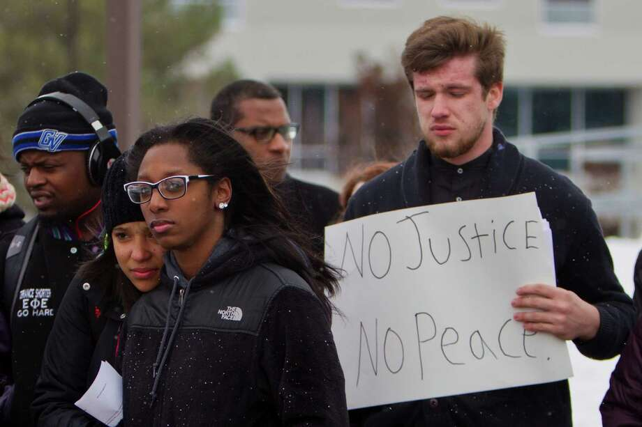 """There was an outpouring of distress nationally following a decision by a St. Louis County grand jury not to indict Officer Darren Wilson in the shooting of unarmed Michael Brown. Grand Valley State junior Jacob Johnston holds a sign that reads """"No Justice No Peace"""" during a rally at the Grand Valley State University clock tower in Allendale, Mich., the day after the decision. Photo: Joel Bissell / Joel Bissell / Associated Press / The Grand Rapids Press"""