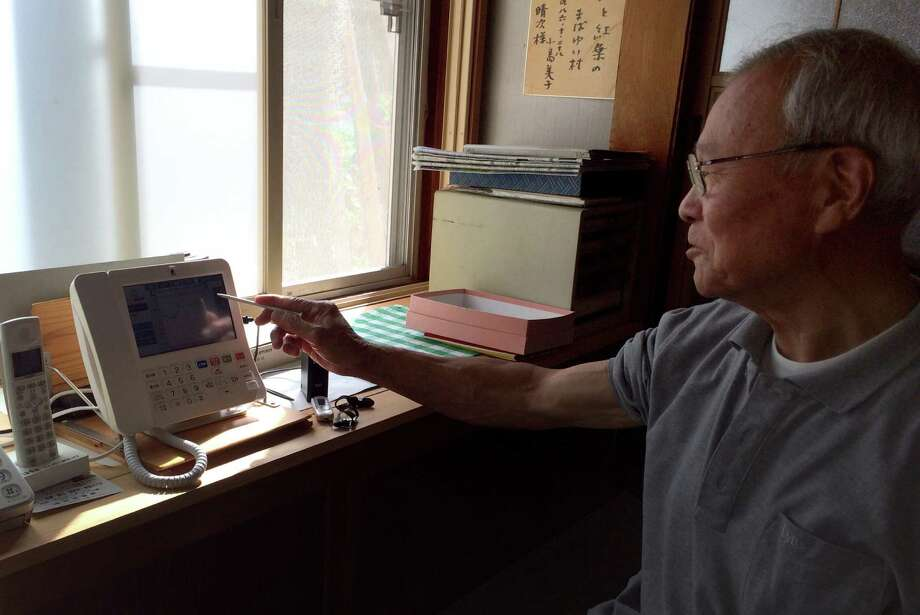 Hirando Hoshi, a retired municipal worker in Hinoemata, Japan, uses a video phone to talk with his village's public health nurse. Photo: David R. Baker / The Chronicle / ONLINE_YES