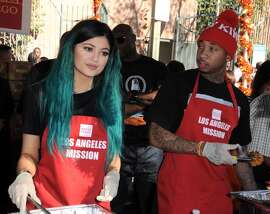 TV personality Kylie Jenner and rapper Tyga attend the Los Angeles Mission And Anne Douglas Center's Thanksgiving Meal For The Homeless held at Los Angeles Mission on November 26, 2014 in Los Angeles, California.