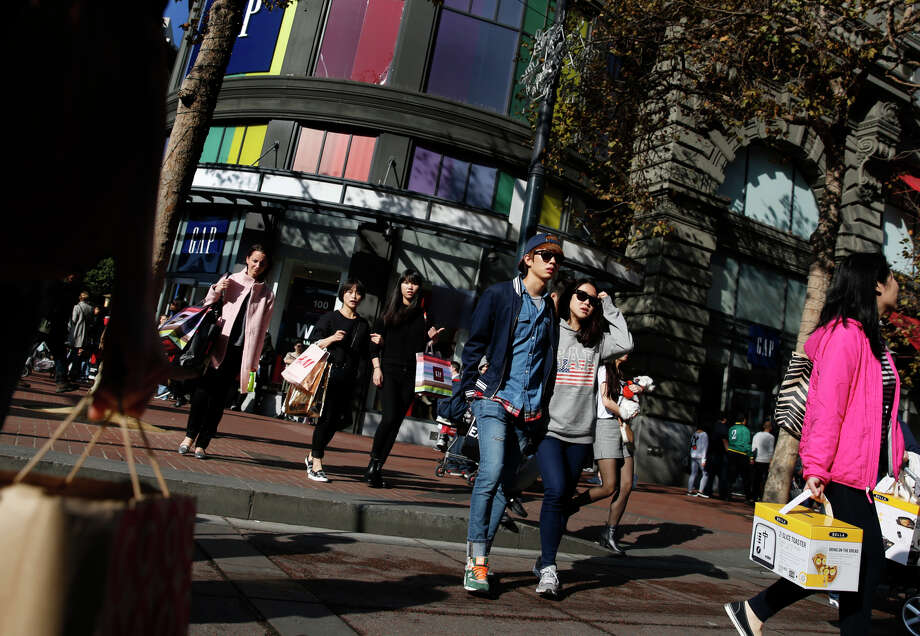 People cross Market Street carrying shopping bags on Black Friday on Friday, November 28, 2014 in San Francisco, Calif. Photo: Lea Suzuki / The Chronicle / ONLINE_YES