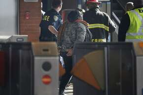 A protester is led through the West Oakland Station by BART police on Nov. 28. The BART board may ask that protesters not be prosecuted.
