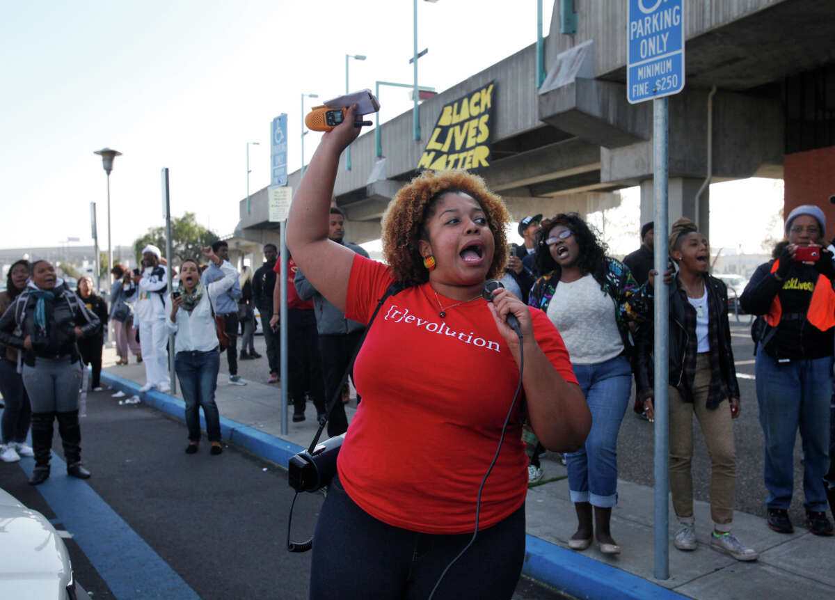 Chinyere Tutashinda of the BlackOut Collective leads the crowd in a chant during a Black Friday protest in at the West Oakland BART station on Nov. 28, 2014.