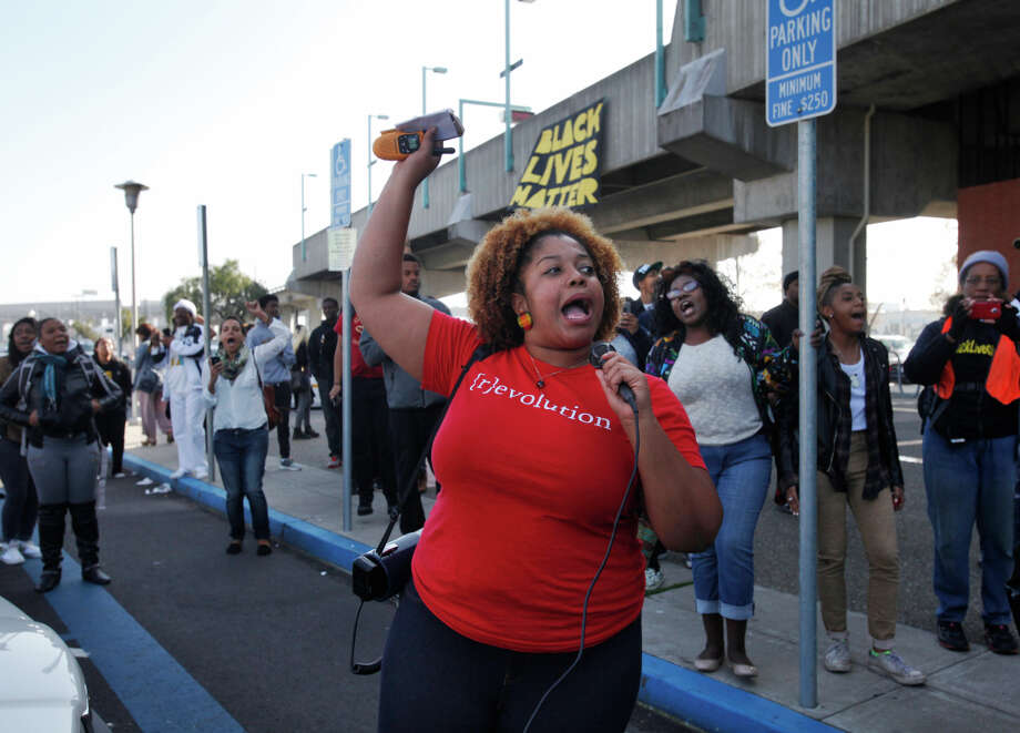 Chinyere Tutashinda of the BlackOut Collective leads the crowd in a chant during a Black Friday protest in at the West Oakland BART station. Photo: Leah Millis / The Chronicle / ONLINE_YES